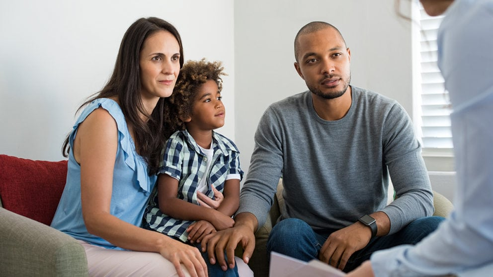 couple sitting on couch at therapy with son