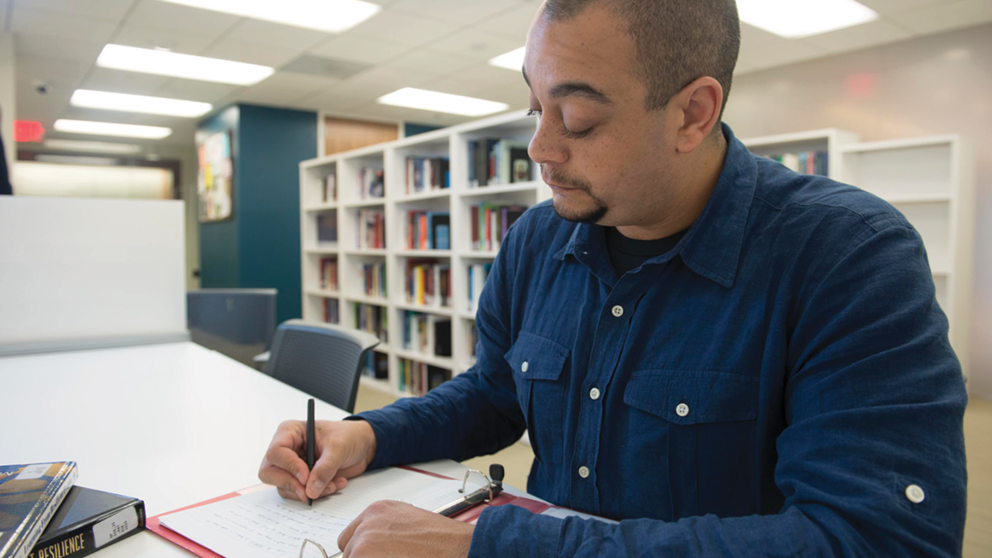 An Applied Behavior Analysis Student works in the library