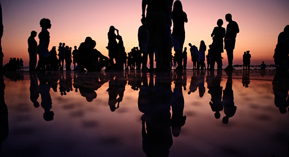people at the beach during pink sunset