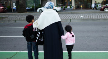 Muslim family about to cross street