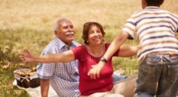 Grandparents at a picnic hugging their grandchild